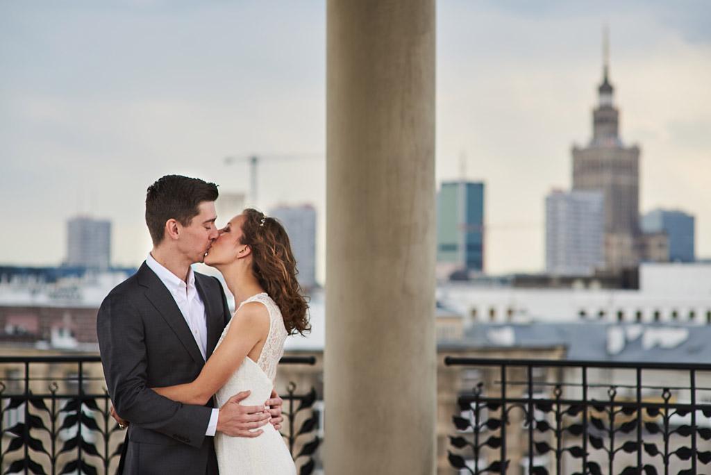 pocałunek pary młodej z warszawą w tle