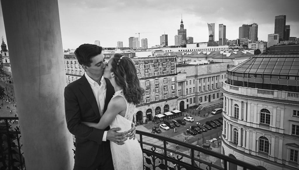 pocałunek pary młodej z centrum Warszawy w tle